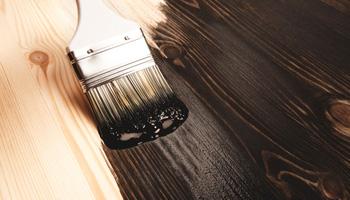 Applying Tar on Wooden Plank