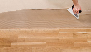 Applying adhesives for wooden flooring